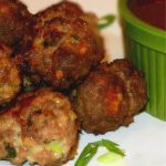 cooked meatballs on a white platter garnished with green onion