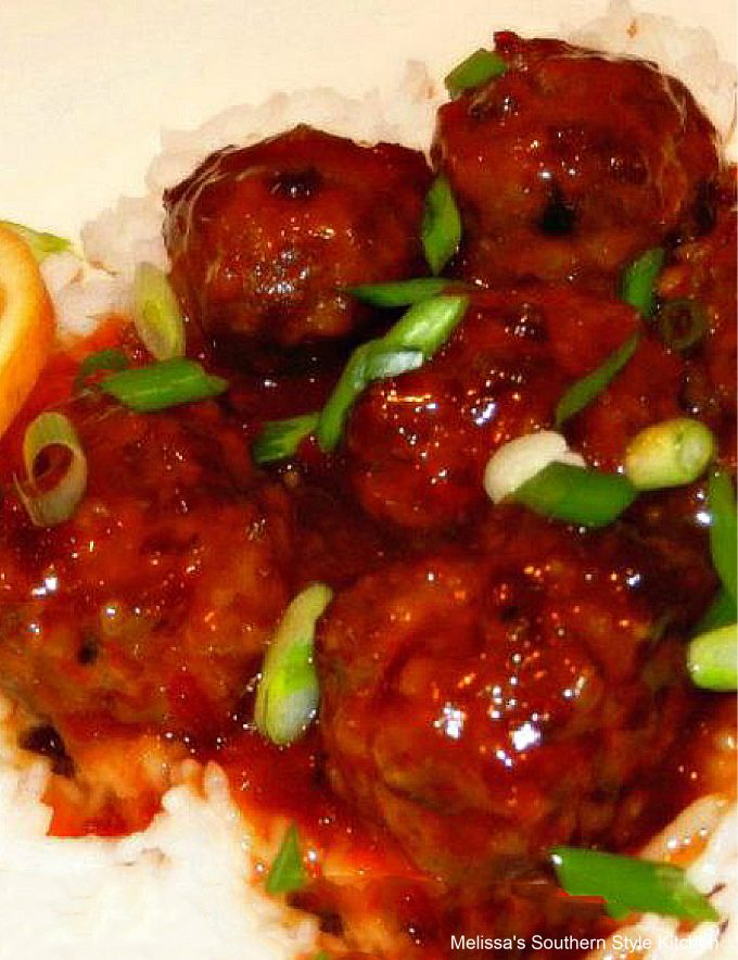 Slow Cooked Asian Meatballs on a white platter with orange chili sauce and rice