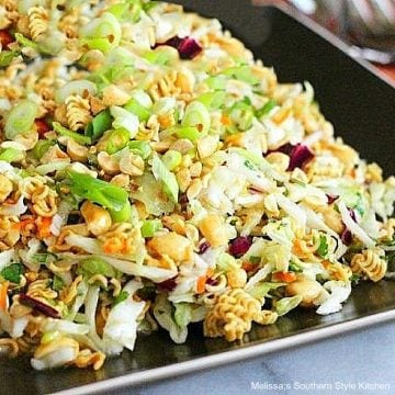 Asian inspired coleslaw with ramen noodles and peanuts in a square brown dish