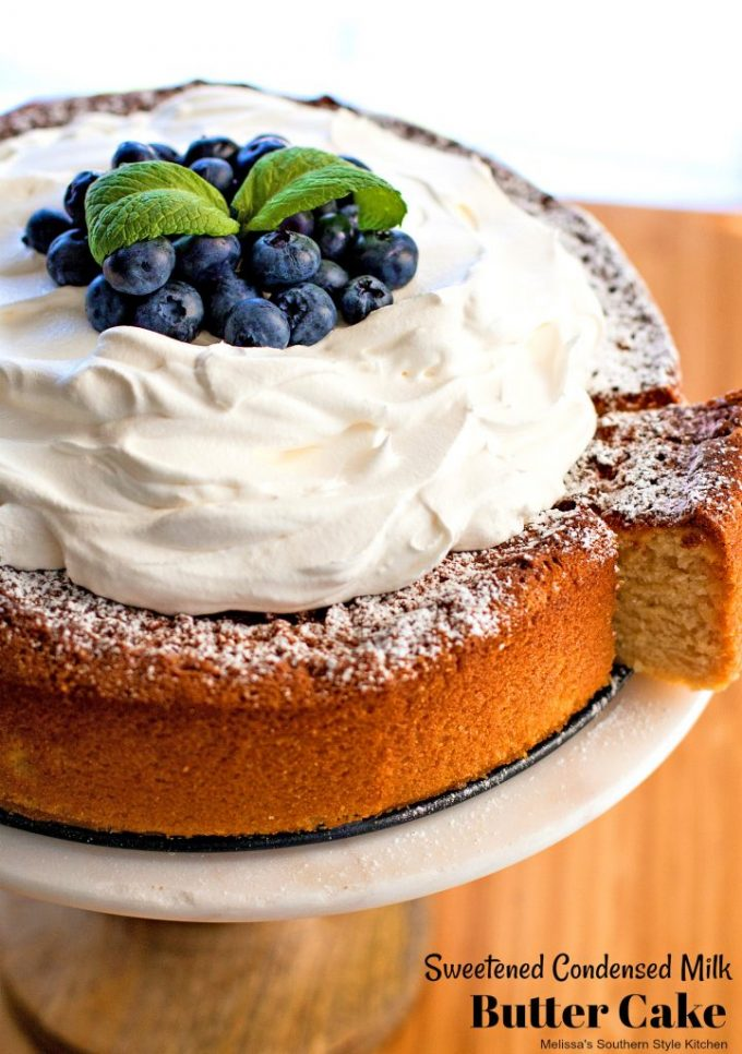 Sweetened Condensed Milk Butter Cake topped with whipped cream and blueberries