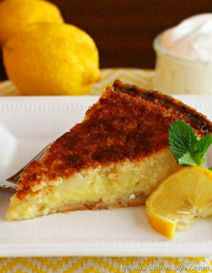 Lemon Buttermilk Pie on a plate with a slice of lemon