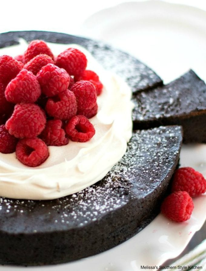 chocolate cake with berries and whipped cream on a cake stand