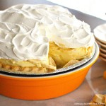 banana cream pie in an orange pie dish with whipped cream on top