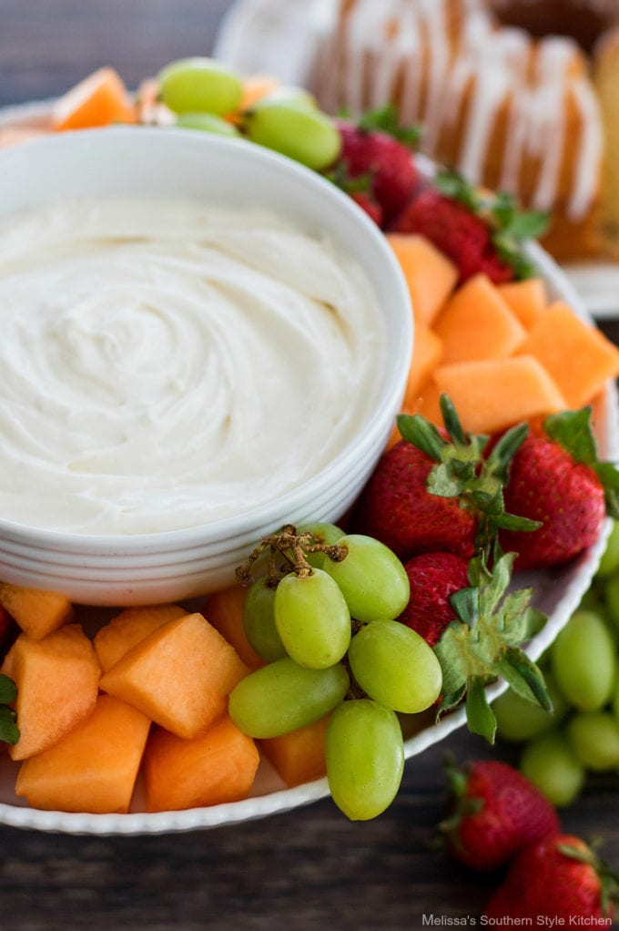fruit dip in a bowl with fresh fruit and cake