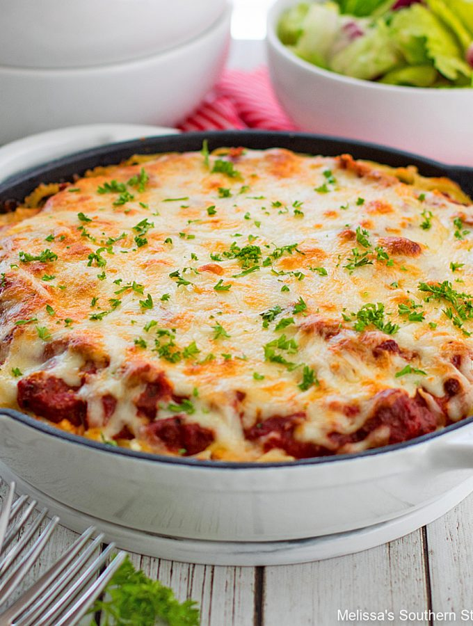 Spaghetti Pie baked in a skillet with a green salad