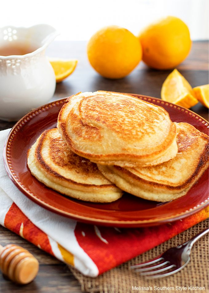 cooked johnnycakes on a red plate with orange wedges and a fork