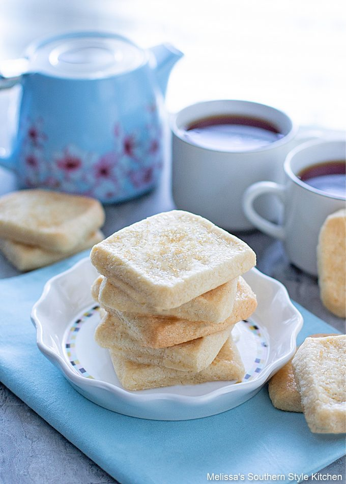 baked shortbread cookies on a white dish with two coffee cups