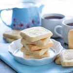 square shortbread cookies on a white plate with a blue tea pot and white tea cups
